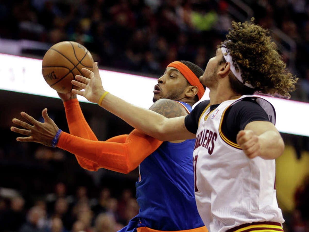 New York Knicks' Carmelo Anthony, center, grabs a rebound against Cleveland Cavaliers' Anderson Varejao, from Brazil, in the second quarter of an NBA basketball game Tuesday, Dec. 10, 2013, in Cleveland. (AP Photo/Mark Duncan)