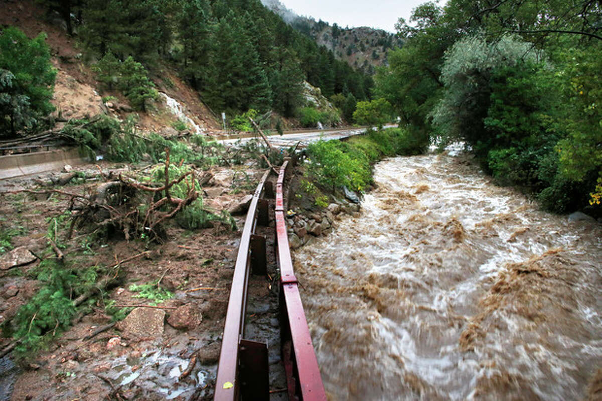 FILE - In this Sept. 13, 2013, file photo, Boulder Creek flows at high speed next to a road closed off by debris from days of rain and flooding, at the base of Boulder Canyon, Colo. When it comes to climate change, local officials have a message for Washington: Lead or get out of the way. Matthew Appelbaum, mayor of Boulder, Colo., says the first thing the federal government should do is not make things worse. He says officials should reconsider policies that encourage rebuilding in flood zones and forested areas vulnerable to wildfires.(AP Photo/Brennan Linsley, File)
