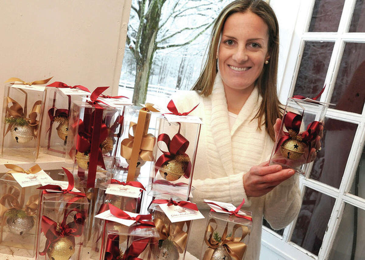 Hour photo / Matthew Vinci Kate Roomet, president of the Wilton Newcomers Club that is holding its annual ornament sale to benefit Wilton Social Services, poses with some of the 50 working bell ornaments. The ornaments are for sale to assist WSS in purchasing gifts for more than 100 Wilton children this holiday season.