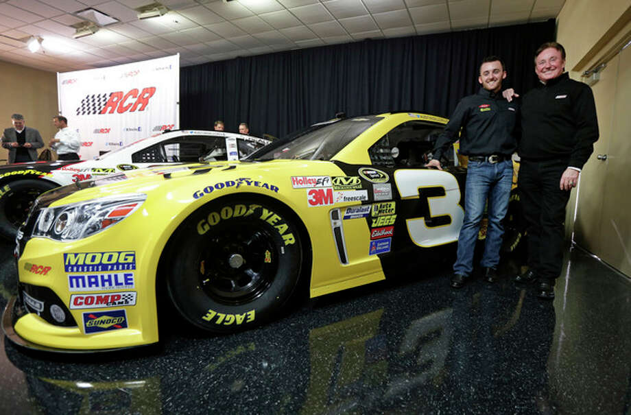 Austin Dillon, left, and team owner Richard Childress, right, pose by one of the cars Dillon will drive in the 2014 NASCAR Sprint Cup series during a news conference at Charlotte Motor Speedway in Concord, N.C., Wednesday, Dec. 11, 2013. The late Dale Earnhardt's famed No. 3 will be back on track in the elite Sprint Cup Series next season with Dillon using the number. (AP Photo/Chuck Burton) / AP