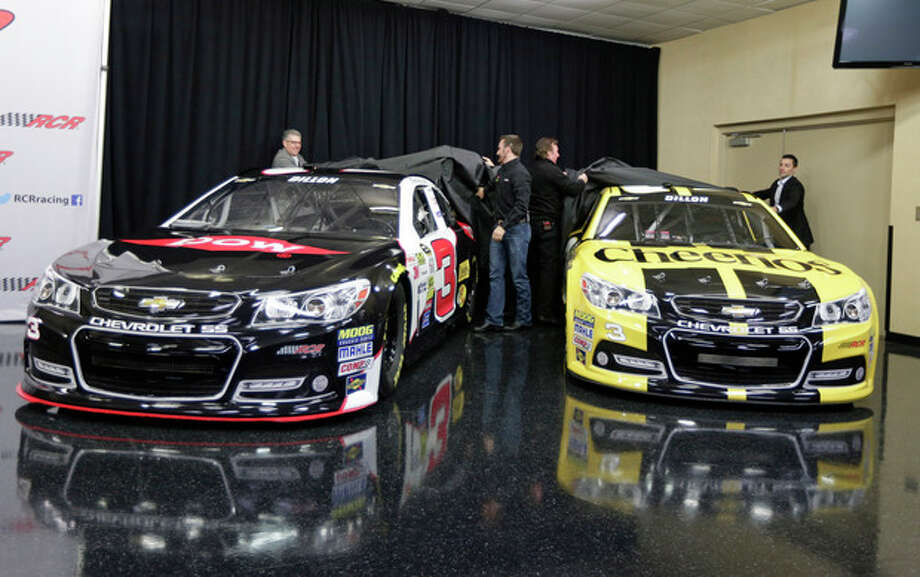 Austin Dillon, center left, and team owner Richard Childress, center right, help unveil the cars Dillon will drive in the 2014 NASCAR Sprint Cup series during a news conference at Charlotte Motor Speedway in Concord, N.C., Wednesday, Dec. 11, 2013. The late Dale Earnhardt's famed No. 3 will be back on track in the elite Sprint Cup Series next season with Dillon using the number. (AP Photo/Chuck Burton) / AP