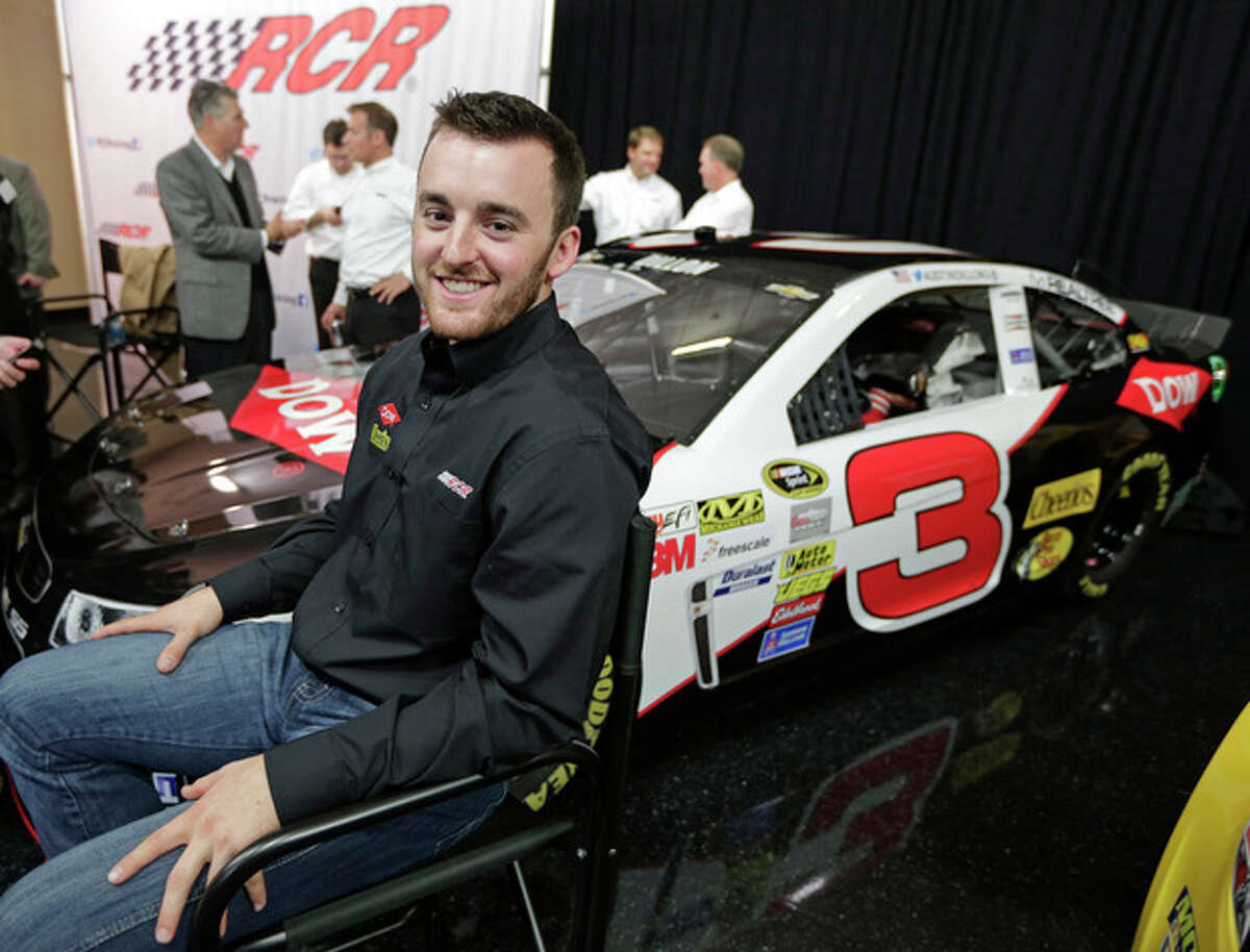 Austin Dillon smiles as he waits to be interviewed in front of the car he will drive in the 2014 NASCAR Sprint Cup series during a news conference at Charlotte Motor Speedway in Concord, N.C., Wednesday, Dec. 11, 2013. The late Dale Earnhardt's famed No. 3 will be back on track in the elite Sprint Cup Series next season with Dillon using the number. (AP Photo/Chuck Burton)