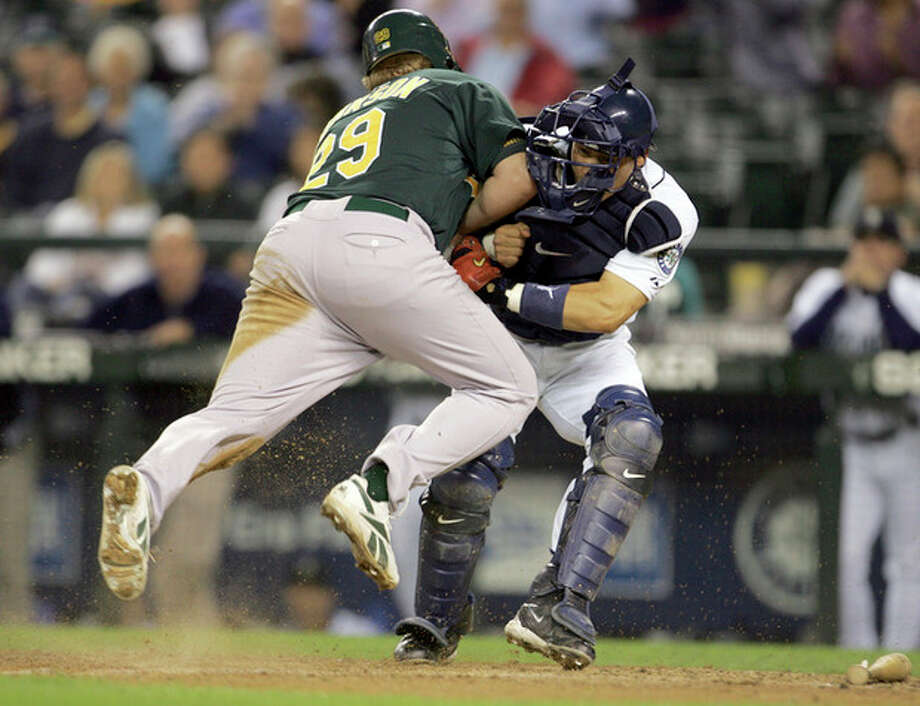 FILE - In this Sept. 27, 2006, file photo, Oakland Athletics' Dan Johnson, left, collides with Seattle Mariners' Kenji Johjima at home plate but was out on the play as Johjima held onto the ball in the ninth inning of a baseball game at Safeco Field in Seattle. New York Mets general manager Sandy Alderson, chairman of the rules committee, announced Wednesday, Dec. 11, 2013, that Major League Baseball plans to eliminate home plate collisions. He said player health and increased awareness of concussions were behind the decision. (AP Photo/Kevin P. Casey, File) / AP