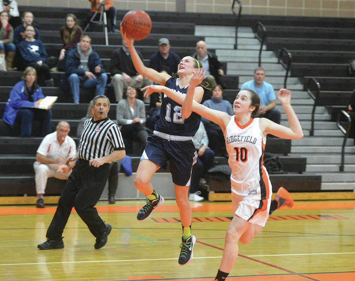 Hour photo/Alex von Kleydorff Wilton's Haley English (12) heads for the hoop ahead of a Ridgefield defender during Wednesday night's game. English had 17 points in the Warriors' 46-39 victory.