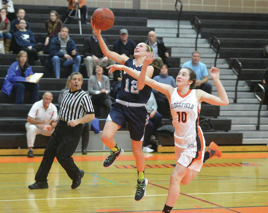 Hour photo/Alex von KleydorffWilton's Haley English (12) heads for the hoop ahead of a Ridgefield defender during Wednesday night's game. English had 17 points in the Warriors' 46-39 victory.