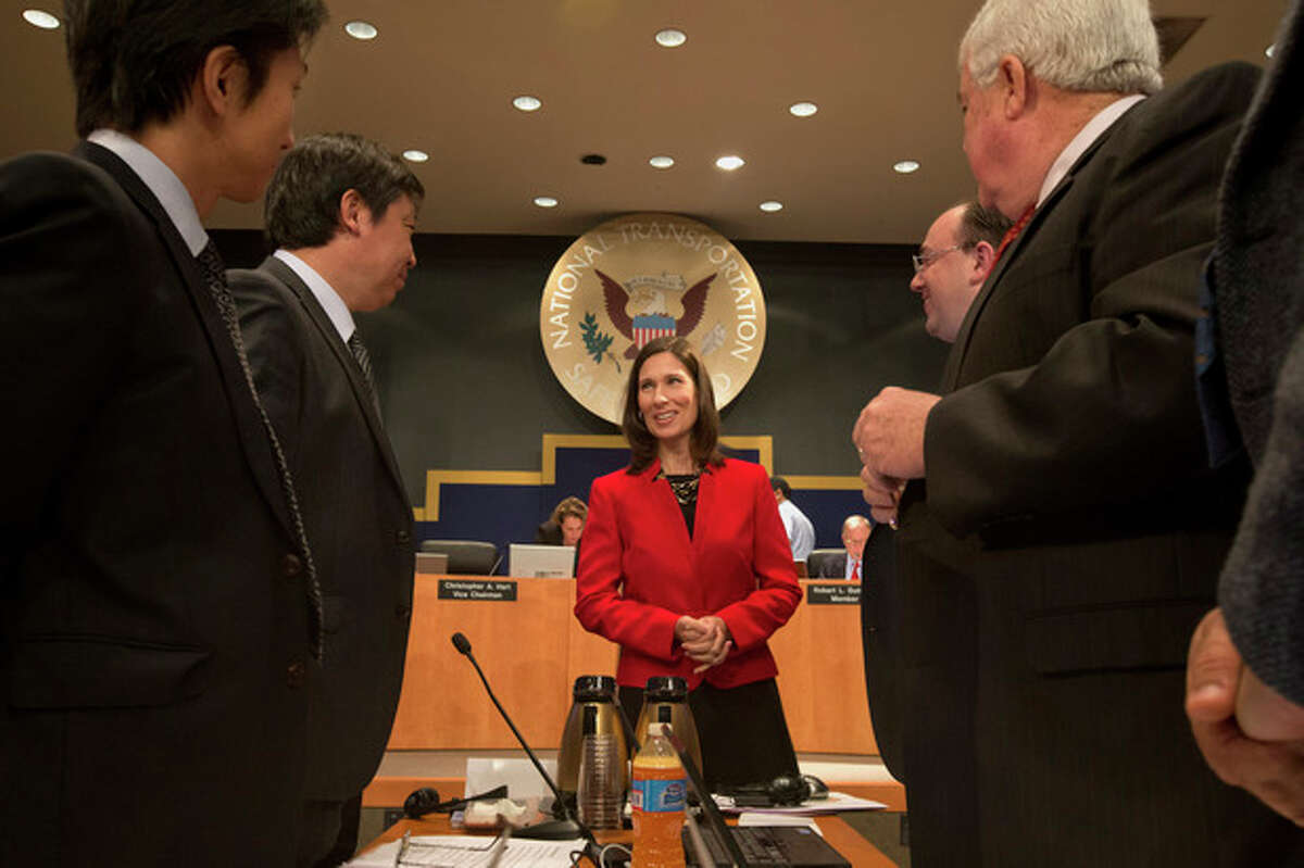 National Transportation Safety Board (NTSB) Chair Deborah Hersman, center, greets representatives of the Asiana Pilots Union at the start of an investigative hearing at the NTSB in Washington, Wednesday, Dec. 11, 2013, on the crash landing of Asiana Airlines Flight 214. The two-dozen witnesses at the hearing include representatives of Asiana, Boeing Co., the Federal Aviation Administration and the Korean government Office of Civil Aviation. (AP Photo/Jacquelyn Martin)
