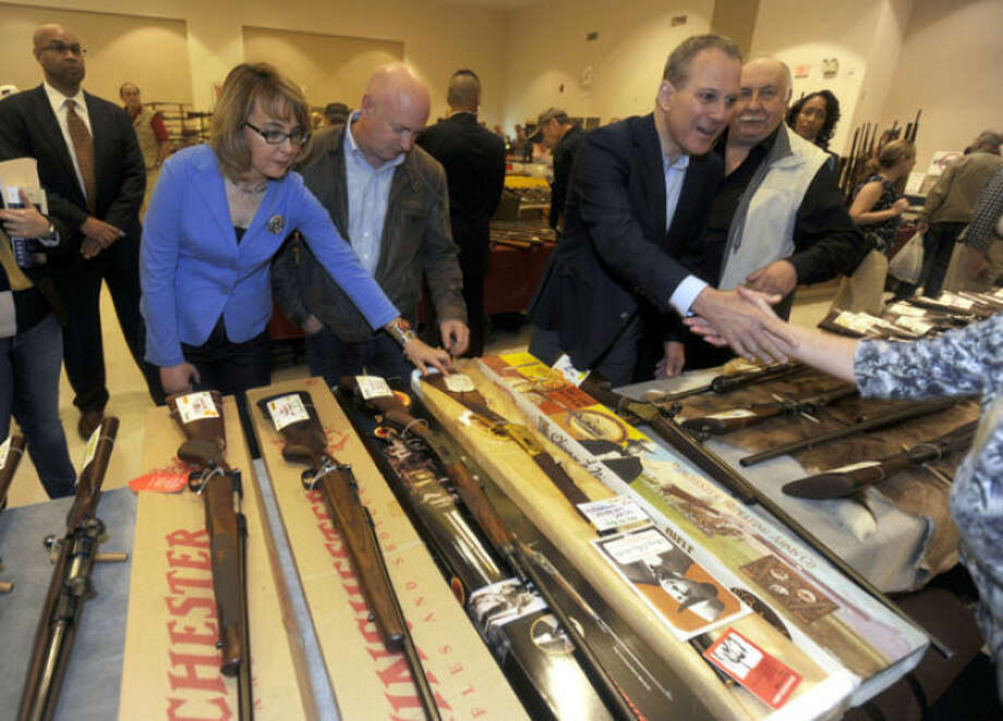FILE - This Oct. 13, 2013 pool-file photo shows former Arizona Rep. Gabby Giffords, her husband Mark Kelly, center, and New York Attorney General Eric Schneiderman, touring the New EastCoast Arms Collectors Associates arms fair in Saratoga Springs, N.Y. A divided Congress denied President Barack Obama's calls for reforms. The federal gun lobby, led by the National Rifle Association, is arguably stronger than ever. And polls suggest that support for new gun laws is slipping as the memory of Newtown's horror fades. (AP Photo/Tim Roske, File, Pool)