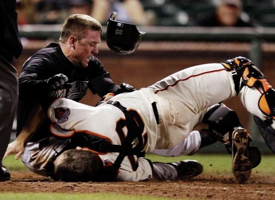 FILE - In this May 25, 2011, file photo, Florida Marlins' Scott Cousins, top, collides with San Francisco Giants catcher Buster Posey on a fly ball hit by Marlins' Emilio Bonifacio during the 12th inning of a baseball game in San Francisco. New York Mets general manager Sandy Alderson, chairman of the rules committee, announced Wednesday, Dec. 11, 2013, that Major League Baseball plans to eliminate home plate collisions. He said player health and increased awareness of concussions were behind the decision. (AP Photo/Marcio Jose Sanchez, File) / AP