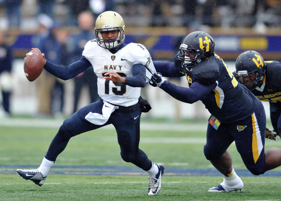 FILE - In this Oct. 19, 2013 file photo, Toledo defensive tackle Treyvon Hester, right, chases Navy quarterback Keenan Reynolds during an NCAA college football game in Toledo, Ohio. Reynolds has enjoyed a sensational sophomore season, running for 1,124 yards and 26 touchdowns. Perhaps the only way it can get better is if he can lead the Midshipmen to their 12th straight win over Army this Saturday in Philadelphia. (AP Photo/David Richard, File) / AP