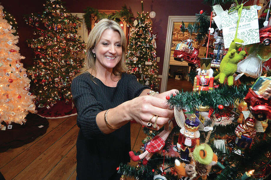 Hour Photo/Alex von Kleydorff Historical Christmas Barn owner Jenifer Bean places an ornament on the tree themed for kids.