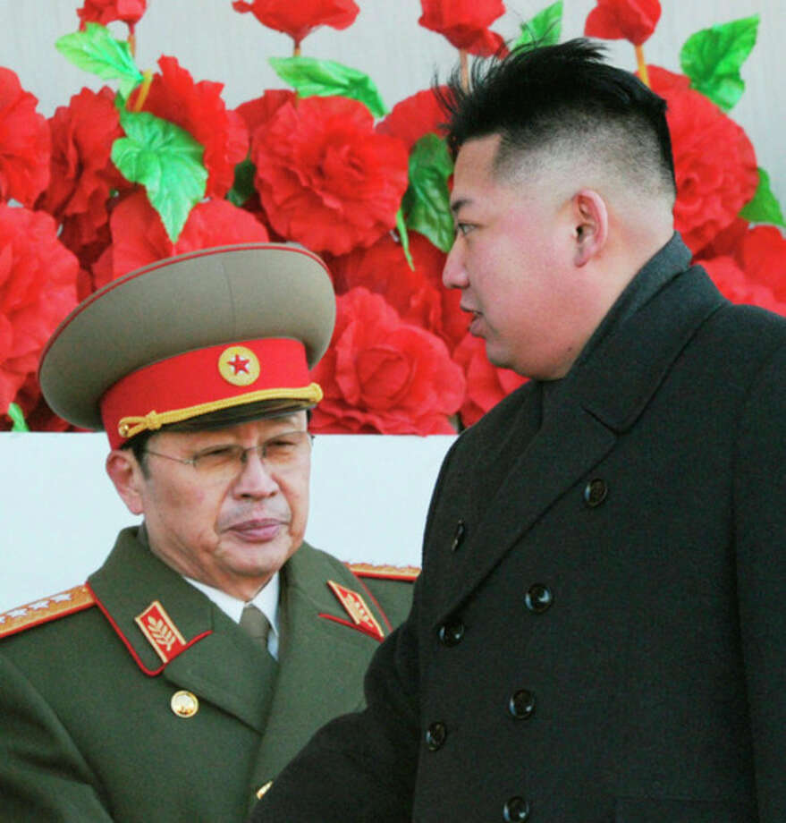 FILE - In this Feb. 16, 2012 file photo, North Korean leader Kim Jong Un walks past his uncle Jang Song Thaek, left, after reviewing a parade of thousands of soldiers and commemorating the 70th birthday of the late Kim Jong Il in Pyongyang, North Korea. North Korean state media say Kim Jong Un's uncle has been executed, calling the leader's former mentor / Kyodo News