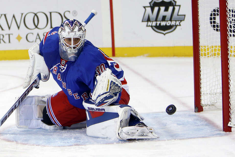 New York Rangers goalie Henrik Lundqvist saves a shot on goal by the Columbus Blue Jackets during the first period of an NHL hockey game Thursday, Dec. 12, 2013, in New York. (AP Photo/Jason DeCrow) / FR103966 AP