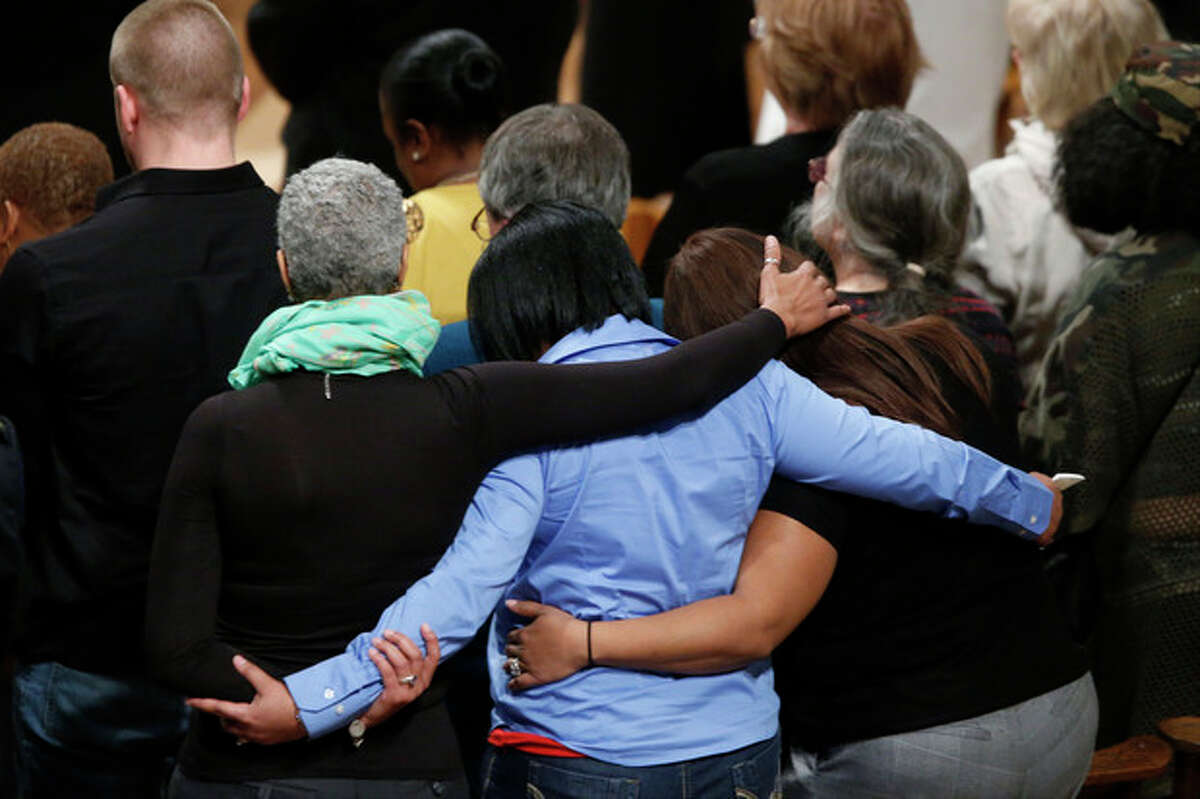 Family members of gun violence embrace each other as they hold a vigil for victims of the shooting at Sandy Hook Elementary School in Newtown, Conn., and other victims of gun violence, Thursday, Dec. 12, 2013, at the National Vigil for Victims of Gun Violence at the National Cathedral in Washington. The one year anniversary of the Newtown, Conn. shootings is December 14. (AP Photo/Charles Dharapak)