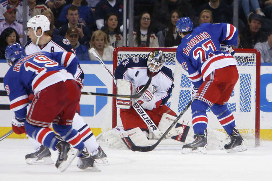 Columbus Blue Jackets goalie Curtis McElhinney saves a shot on goal from New York Rangers' Brad Richards (19) as Ryan McDonagh (27) looks on during the first period of an NHL hockey game Thursday, Dec. 12, 2013, in New York. (AP Photo/Jason DeCrow) / FR103966 AP