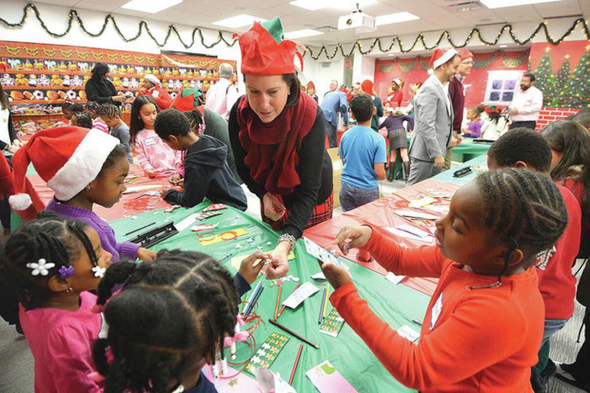 Hour Photo/Alex von Kleydorff. Beirsdorf's Maribeth Devine helps the kids with their Christmas projects at the company's Winter Wonderland