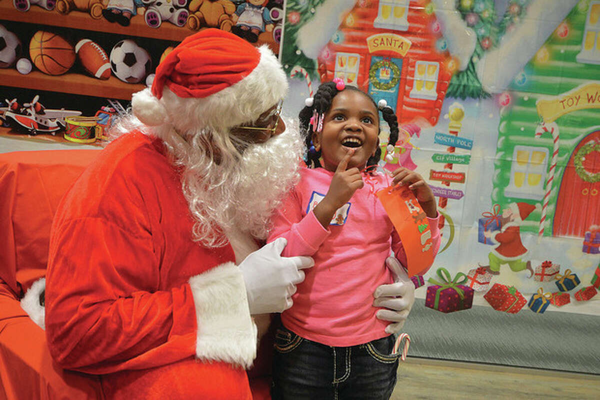 Hour Photo/Alex von Kleydorff. 5 yr old Brandy Fritz thinks about what she wants for Christmas as she visits with Santa Clause at Beirsdorf Inc. in Wilton