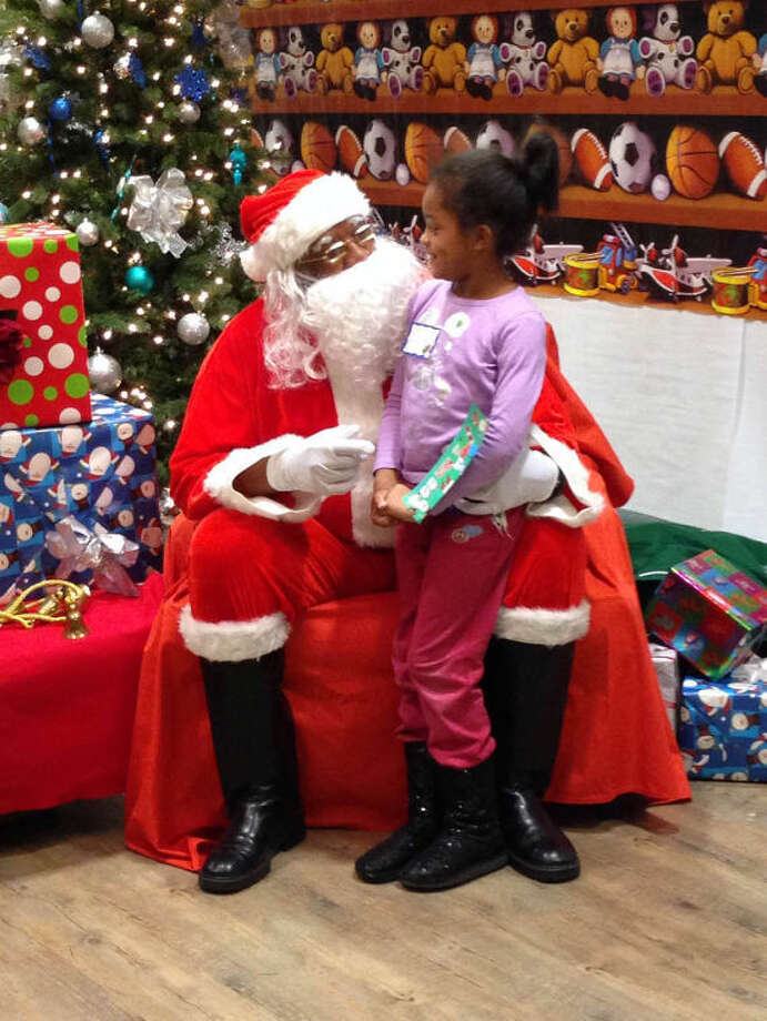 Santa talks to children at Beiersdorf holiday party.