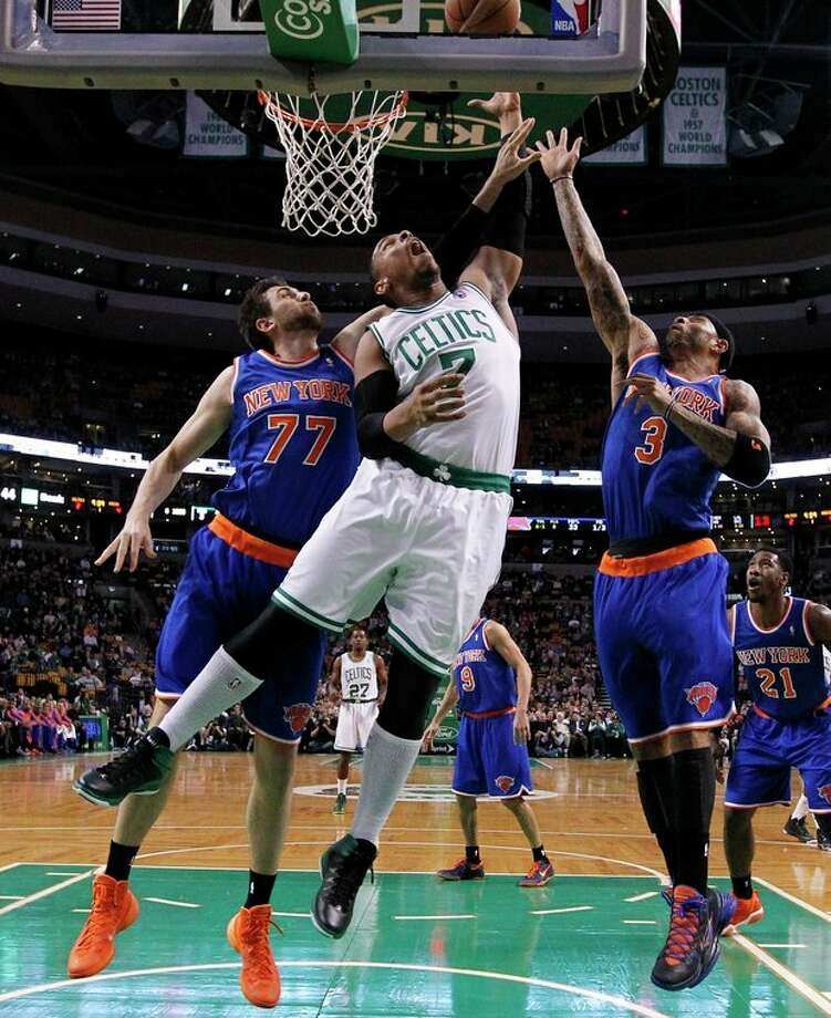 Boston Celtics' Jared Sullinger (7) battles New York Knicks' Andrea Bargnani (77) and Kenyon Martin (3) for a rebound in the first quarter of an NBA basketball game in Boston, Friday, Dec. 13, 2013. (AP Photo/Michael Dwyer) / AP