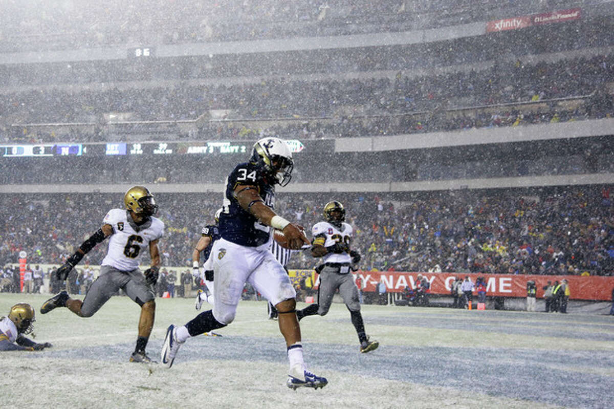 Navy fullback Noah Copeland (34) runs in a touchdown past Army's linebacker Geoffery Bacon (6) and defensive back Josh Jenkins (39) during the first half of an NCAA college football game, Saturday, Dec. 14, 2013, in Philadelphia. (AP Photo/Matt Slocum)