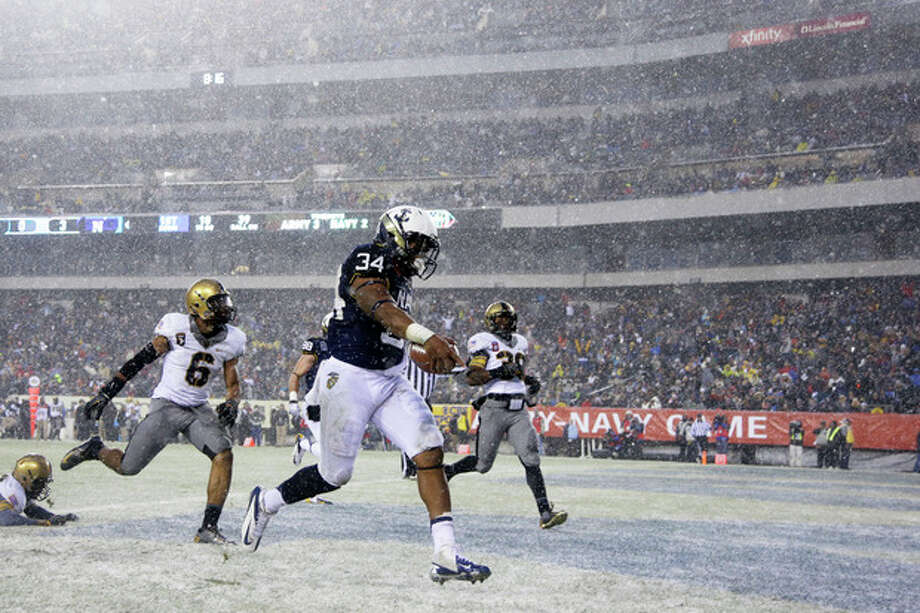 Navy fullback Noah Copeland (34) runs in a touchdown past Army's linebacker Geoffery Bacon (6) and defensive back Josh Jenkins (39) during the first half of an NCAA college football game, Saturday, Dec. 14, 2013, in Philadelphia. (AP Photo/Matt Slocum) / AP