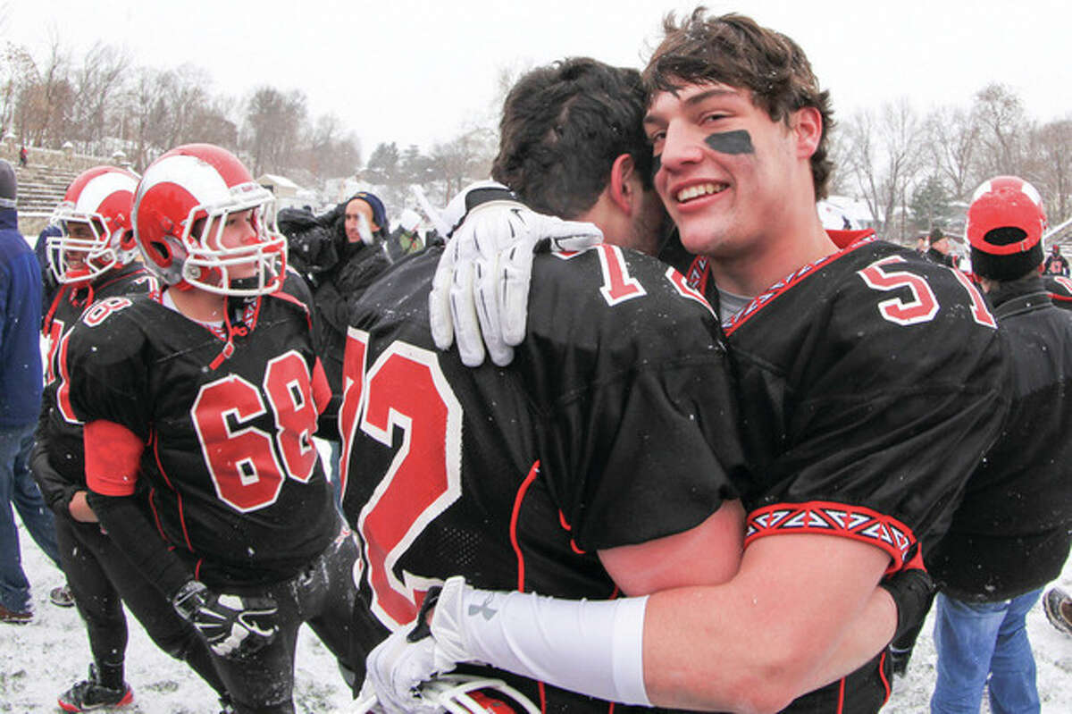 Hour Photo Chris Palermo Beau Santero, right, hugs captain Joao Rocha amongst the sea of fans that rushed the field after New Canaan's victory against Dariens in the CIAC football championships Stamford High School Saturday.
