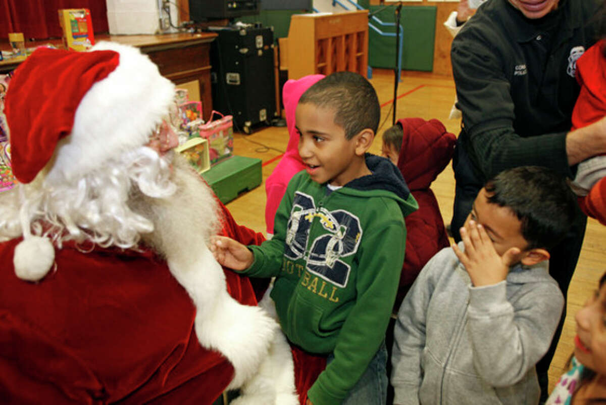 Hour photo / Danielle Calloway Jeremiah Delgado, 6, meets Santa at the annual Children's Holiday Party, sponsored by the Norwalk PAL. The event was hosted by the Norwalk Police Community Policing Division at Columbus Magnet School in Norwalk Saturday afternoon.