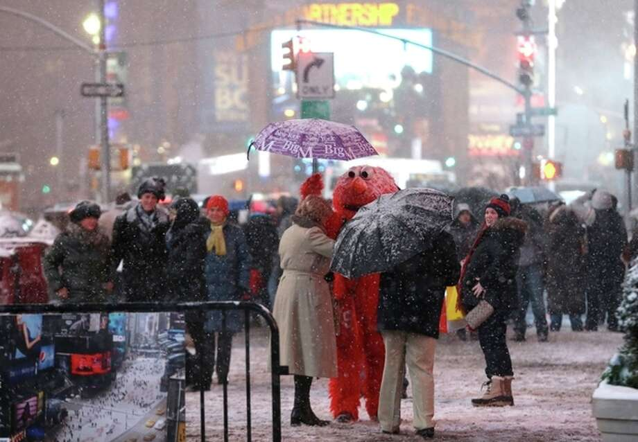A person wearing an Elmo outfit holds an umbrella for a woman as she searches for money to give to the character after posing for a photo together at Times Square, Saturday, Dec. 14, 2013, in New York. Manhattan is experiencing heavy snow with reports saying the weather will continue to cover the city with snow throughout the night. (AP Photo/Julio Cortez) / AP