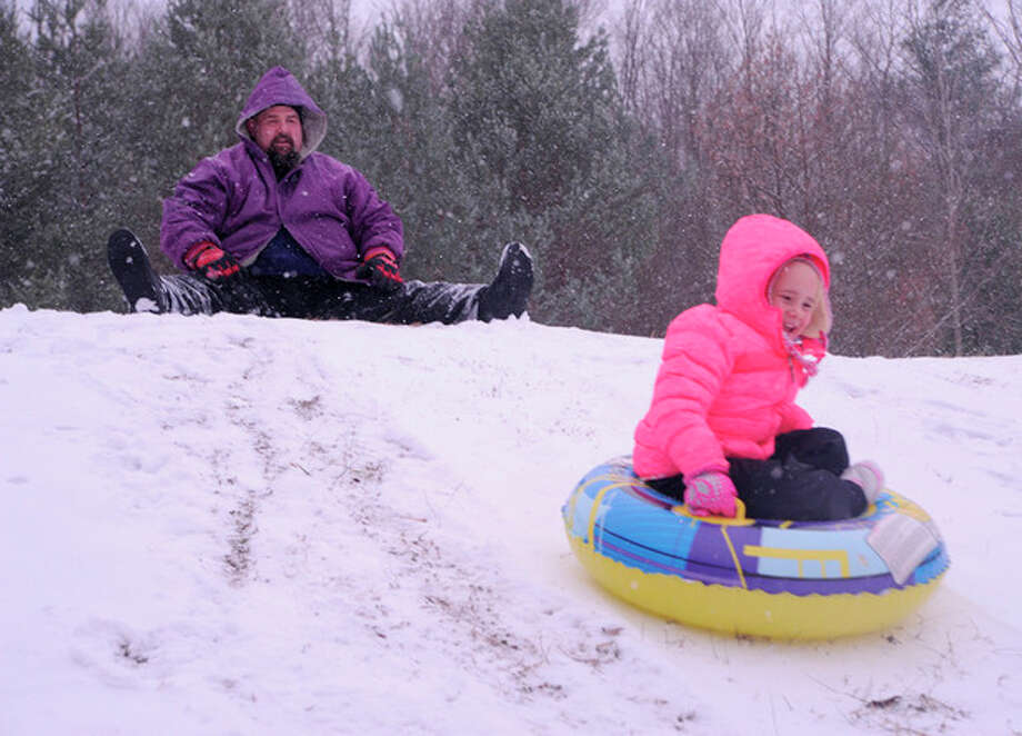 Bob Nye, left, sends his daughter Elizabeth, 5, down a snowy hill outside of the Shamokin Area Elementary School on Saturday, Dec. 14, 2013. (AP Photo/The News-Item, Mike Staugaitis) / The News-Item