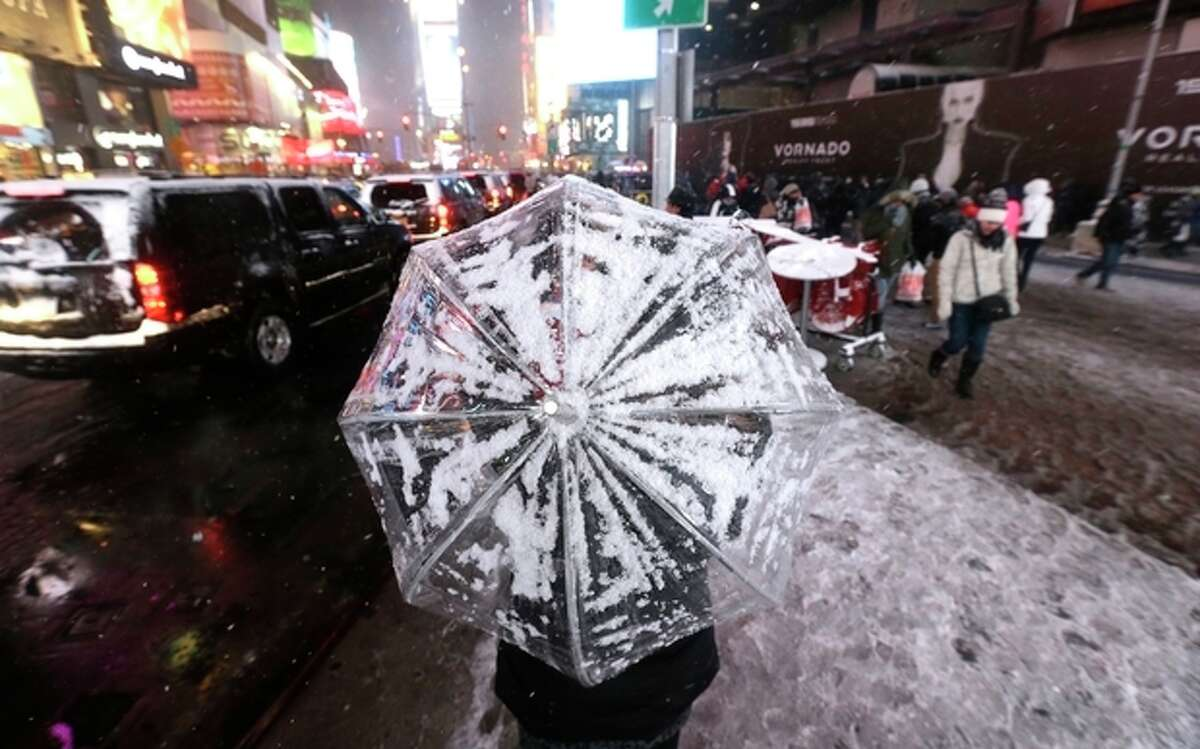 A woman uses an umbrella to cover herself from snow at Times Square, Saturday, Dec. 14, 2013, in New York. Manhattan is experiencing heavy snow with reports saying the weather will continue to cover the city with snow throughout the night. (AP Photo/Julio Cortez)