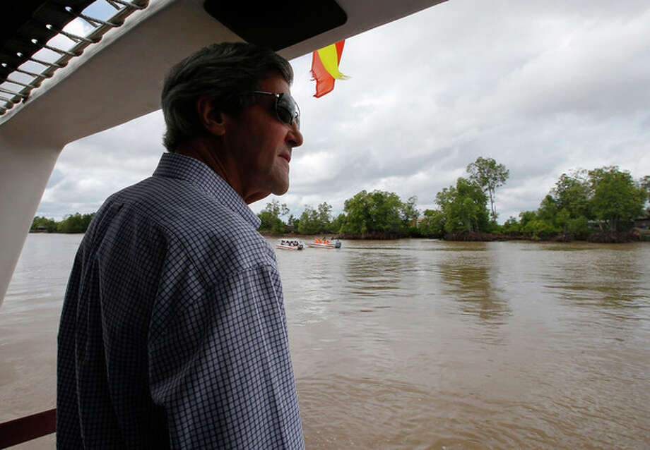 U.S. Secretary of State John Kerry rides a boat through the Mekong River Delta Sunday, Dec. 15, 2013. Along the winding muddy waters of the Mekong Delta where he once patrolled for communist insurgents on a naval gunboat, Secretary of State Kerry turned his sights Sunday on a new enemy: climate change. (AP Photo/Brian Snyder, Pool) / REUTERS POOL