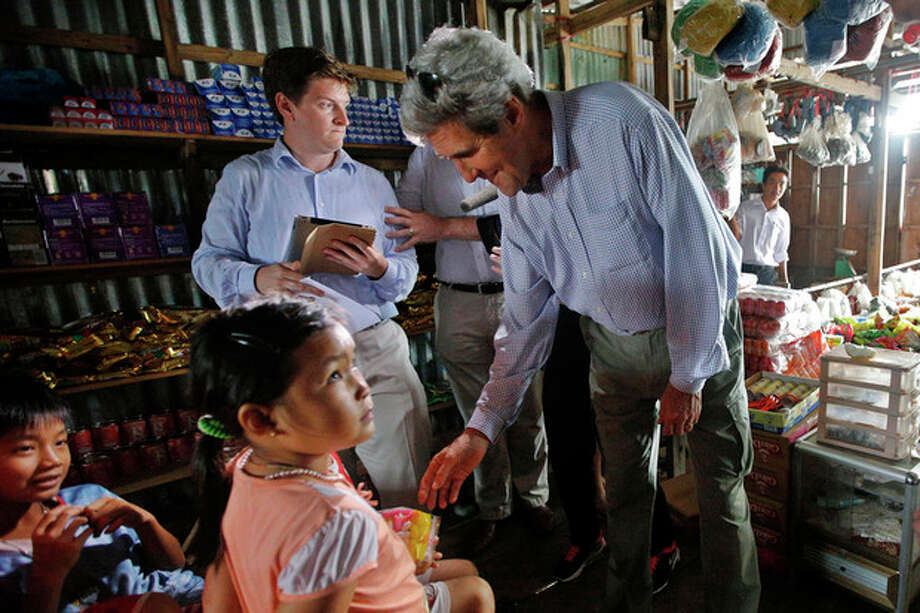 U.S. Secretary of State John Kerry, right, gives a bag of cookies to children in a shop in Kien Vang along the Mekong River Delta Sunday, Dec. 15, 2013. Along the winding muddy waters of the Mekong Delta where he once patrolled for communist insurgents on a naval gunboat, Secretary of State Kerry turned his sights Sunday on a new enemy: climate change. (AP Photo/Brian Snyder, Pool) / REUTERS POOL