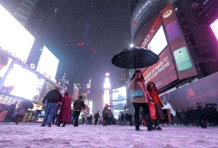 A woman uses an umbrella to cover herself from snow at Times Square, Saturday, Dec. 14, 2013, in New York. Manhattan is experiencing heavy snow with reports saying the weather will continue to cover the city with snow throughout the night. (AP Photo/Julio Cortez) / AP