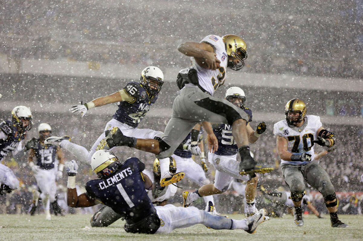 Army running back Terry Baggett (31) jumps over defender Navy cornerback Brendon Clements (1) during the first half of an NCAA college football game, Saturday, Dec. 14, 2013, in Philadelphia. (AP Photo/Matt Rourke)