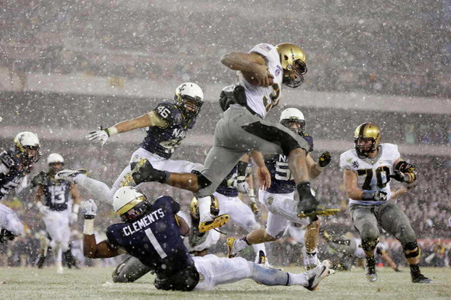 Army running back Terry Baggett (31) jumps over defender Navy cornerback Brendon Clements (1) during the first half of an NCAA college football game, Saturday, Dec. 14, 2013, in Philadelphia. (AP Photo/Matt Rourke) / AP