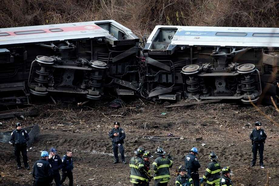 FILE- In this Dec. 1, 2013 file photo, emergency personnel respond to the scene of a Metro-North passenger train derailment in the Bronx borough of New York. Metro-North trains are equipped with an automatic breaking system that might have prevented the crash, but the system was in place to regulate the distance between trains, not to control speeds as trains approached curves, or passed over hills and bridges. Since the crash, the speed limit was lowered on the approach to the curve, plus an alarm will sound and an automatic braking system will engage is a train approaches the bend too fast. (AP Photo/John Minchillo, File) / FR61802 AP