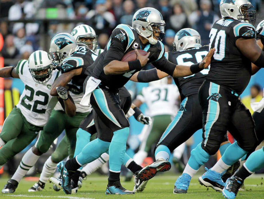 Carolina Panthers' Cam Newton, center, rushes for a first down against the New York Jets during the first half of an NFL football game in Charlotte, N.C., Sunday, Dec. 15, 2013. (AP Photo/Bob Leverone) / FR170480 AP