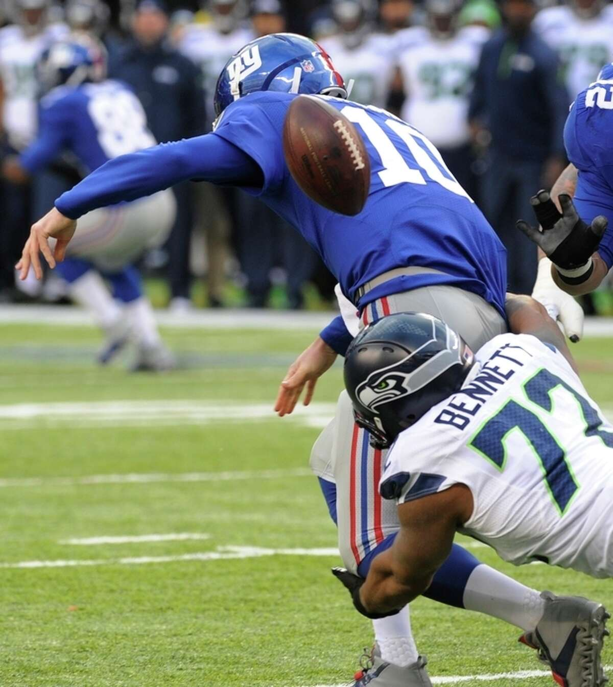 Seattle Seahawks defensive end Michael Bennett (72) forces a fumble by New York Giants quarterback Eli Manning (10) during the second half of an NFL football game on Sunday, Dec. 15, 2013, in East Rutherford, N.J. The Giants recovered the fumble on the play. (AP Photo/Bill Kostroun)