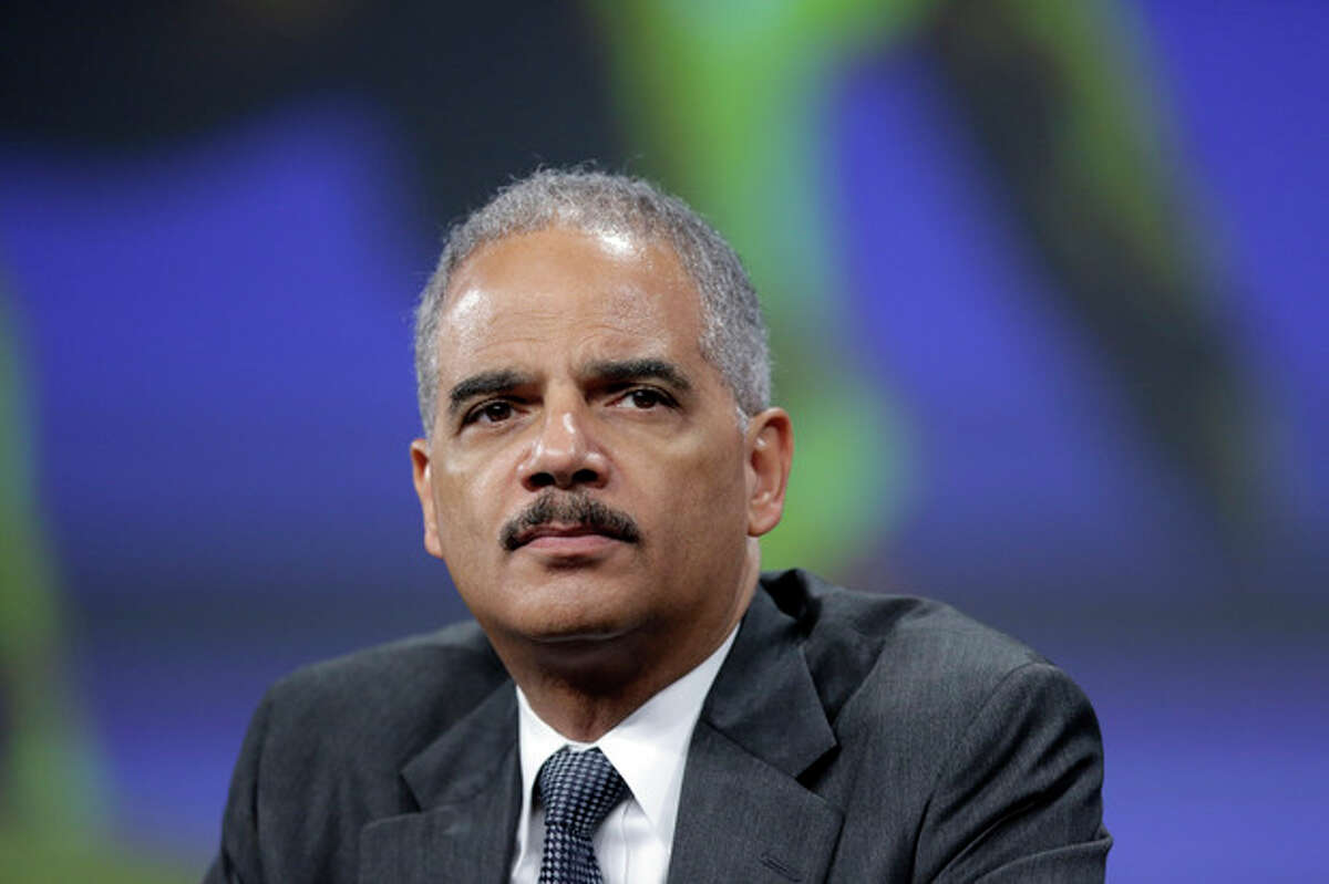 FILE - In this Oct. 21, 2013 file photo, Attorney General Eric Holder listens to a speech after of his remarks during the Annual International Association of Chiefs of Police Conference, at the Pennsylvania Convention Center in Philadelphia. The FBI has helped to disrupt or prevent nearly 150 shootings and violent attacks in 2013 alone, in part by steering potential gunmen toward mental health professionals. There have been hundreds of these disruptions since 2011, Attorney General Eric Holder told an audience of police chiefs in October, touting the behind-the-scenes work of a small FBI unit based out of Quantico, Va. (AP Photo/Matt Rourke)