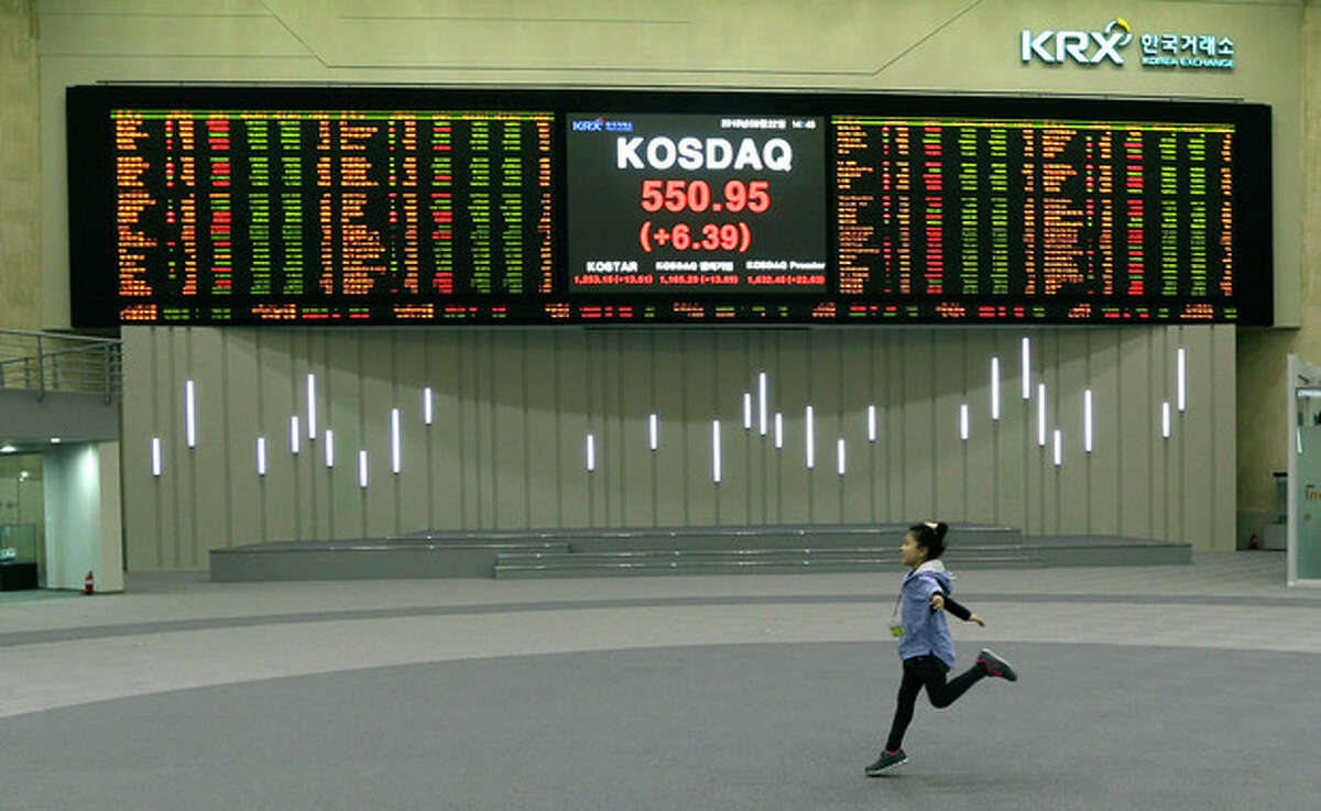 FILE -In this Friday, March 22, 2013, file photo, a girl plays near a screen showing the stock prices at the Korea Exchange in Seoul, South Korea. The Federal Reserve?'s super-low interest-rate policy has inflated a slew of dangerous asset bubbles, just this year, the S&P 500 has jumped 26 percent. That increase corresponds with the Fed announcement last December that it would buy $85 billion of bonds each month. This has been the third attempt at bond purchasing by the Fed. Since the first round of buying at the end of 2008, stocks have climbed 124 percent. The strong increase raises suspicions of a bubble, given that stocks are performing so well in an otherwise sluggish recovery. (AP Photo/Lee Jin-man, File)