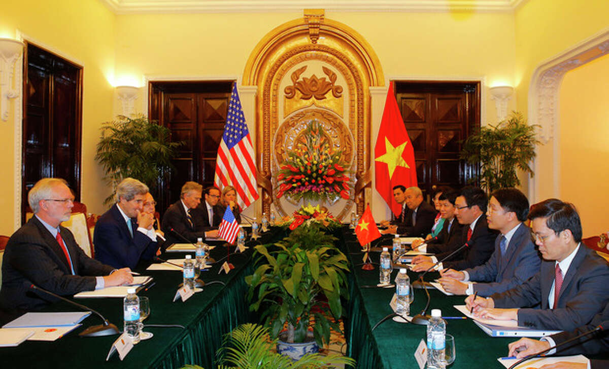 U.S. Secretary of State John Kerry, second left, talks with Vietnamese Foreign Minister Pham Binh Minh, third right, in Hanoi Monday, Dec. 16, 2013. Secretary of State Kerry is in Vietnam pressing the communist country on democratic and economic reforms and offering U.S. assistance to protect its maritime borders. (AP Photo/Brian Snyder, Pool)