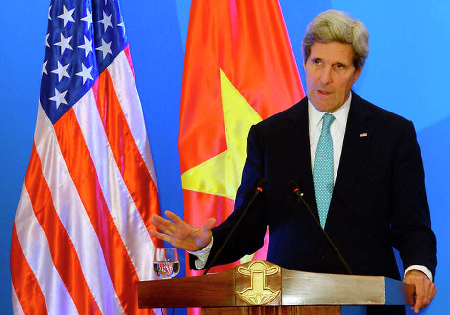 U.S. State Secretary John Kerry speaks during a joint press conference with Vietnamese Foreign Minister Pham Binh Minh in Hanoi Monday, Dec. 16, 2013. The United States will boost maritime security assistance to China's smaller neighbors amid rising tensions over disputed territories in the South China Sea, Kerry announced on Monday during a visit to Vietnam, where he also pressed the communist government on human rights and democratic and economic reforms. (AP Photo/Hoang Dinh Nam, Pool) / AFP POOL