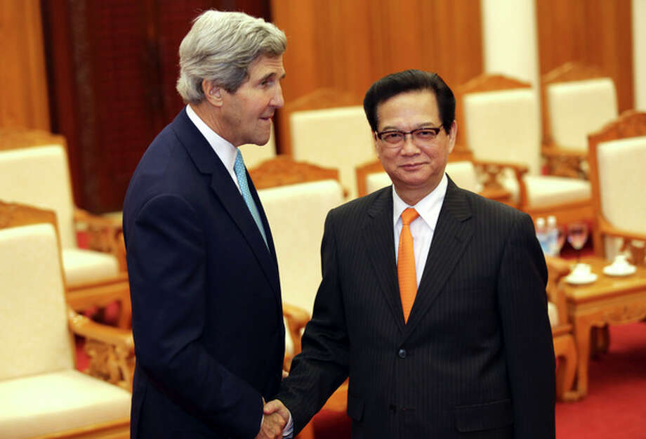 U.S. Secretary of State John Kerry, left, shakes hand with Vietnamese Prime Minister Nguyen Tan Dung in Hanoi, Vietnam Monday, Dec. 16, 2013. The United States will boost maritime security assistance to China's smaller neighbors amid rising tensions over disputed territories in the South China Sea, Kerry announced on Monday during a visit to Vietnam, where he also pressed the communist government on human rights and democratic and economic reforms.(AP Photo/Na Son Nguyen, Pool) / NasonNguyen(C)copyrighted.