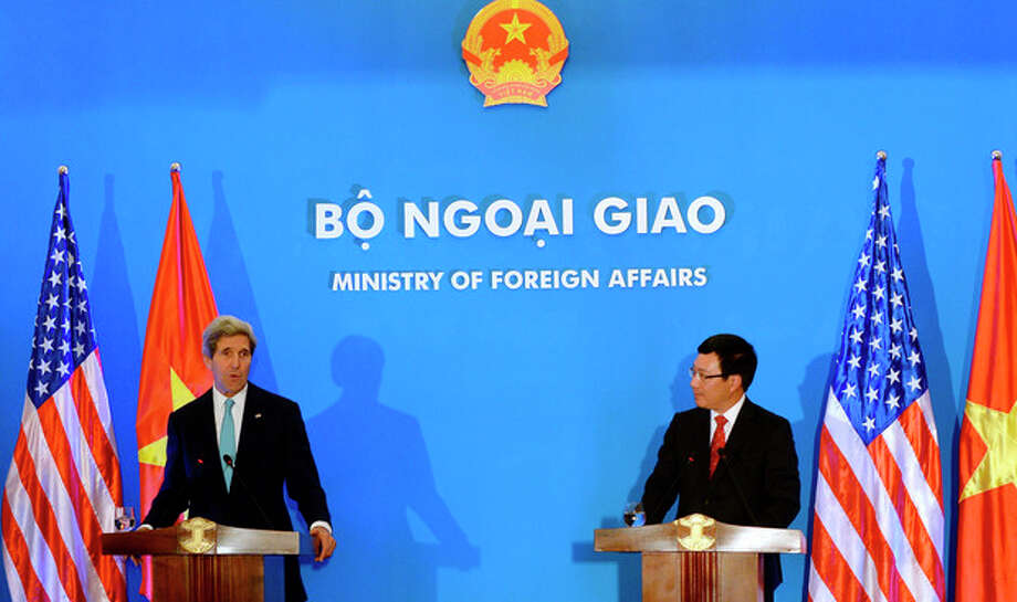 U.S. Secretary of State John Kerry, left, speaks during a joint press conference with Vietnamese Foreign Minister Pham Binh Minh in Hanoi Monday, Dec. 16, 2013. The United States will boost maritime security assistance to China's smaller neighbors amid rising tensions over disputed territories in the South China Sea, Kerry announced on Monday during a visit to Vietnam, where he also pressed the communist government on human rights and democratic and economic reforms. (AP Photo/Hoang Dinh Nam, Pool) / AFP POOL