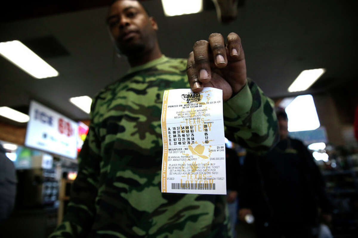 John Hollis shows off his Mega Millions lottery ticket he purchased at the Fuel City convenience story Monday, Dec. 16, 2013, in Dallas. The Mega Millions jackpot soared to $586 million on Monday amid a frenzy of ticket purchases, a jump that pushed the prize closer to the $656 million U.S. record set last year. (AP Photo/LM Otero)