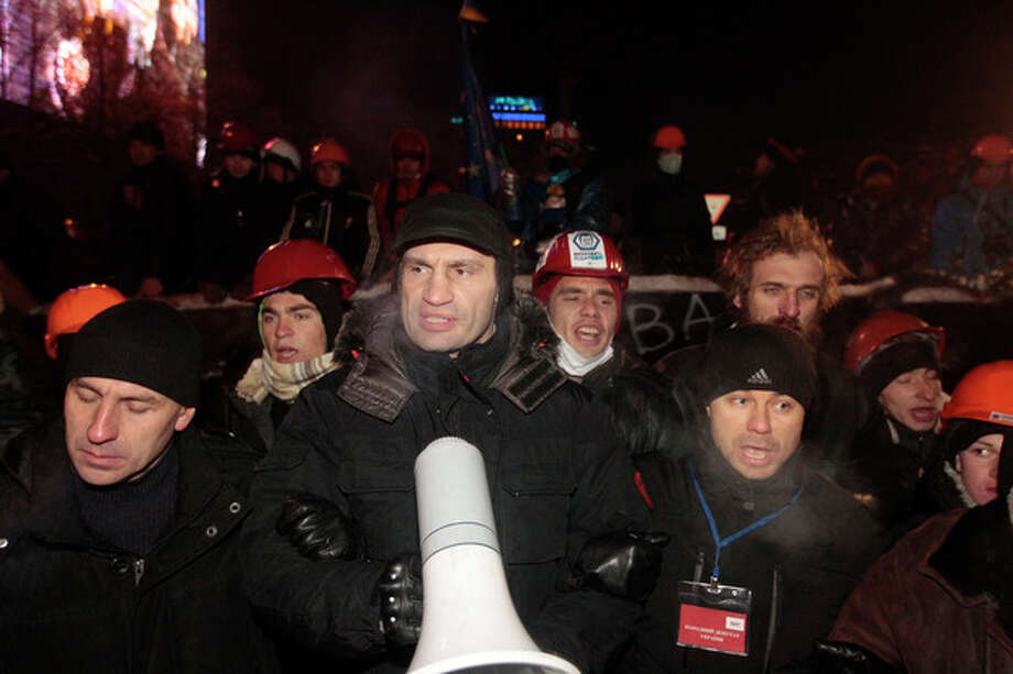 Ukrainian lawmaker and chairman of the opposition party Udar (Punch), WBC heavyweight boxing champion Vitali Klitschko, center, and Pro-European Union activists face Ukrainian riot policemen at their tent camps on the Independence Square in Kiev, Ukraine, Wednesday, Dec. 11, 2013. Security forces clashed with protesters as they began tearing down opposition barricades and tents set up in the center of the Ukrainian capital early Wednesday, in an escalation of the weeks-long standoff threatening the leadership of President Viktor Yanukovych. (AP Photo/Sergei Grits) / AP