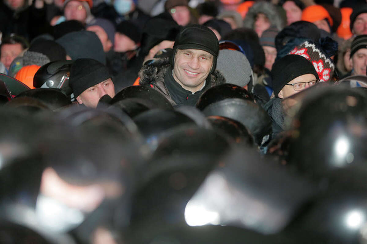 Ukrainian lawmaker and chairman of the opposition party Udar (Punch), WBC heavyweight boxing champion Vitali Klitschko, center, smiles in front of riot police during clashes between police and pro-European Union activists in Kiev, Ukraine, Wednesday, Dec. 11, 2013. Security forces clashed with protesters as they began tearing down opposition barricades and tents set up in the center of the Ukrainian capital early Wednesday, in an escalation of the weeks-long standoff threatening the leadership of President Viktor Yanukovych. (AP Photo/Efrem Lukatsky)