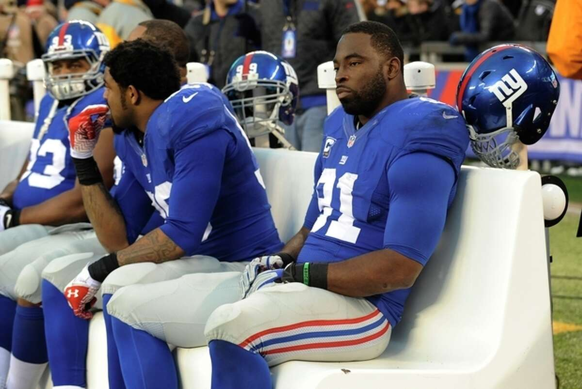 New York Giants defensive end Justin Tuck, right, sits on the bench in the final minutes of an NFL football game against the Seattle Seahawks, Sunday, Dec. 15, 2013, in East Rutherford, N.J. (AP Photo/Bill Kostroun)