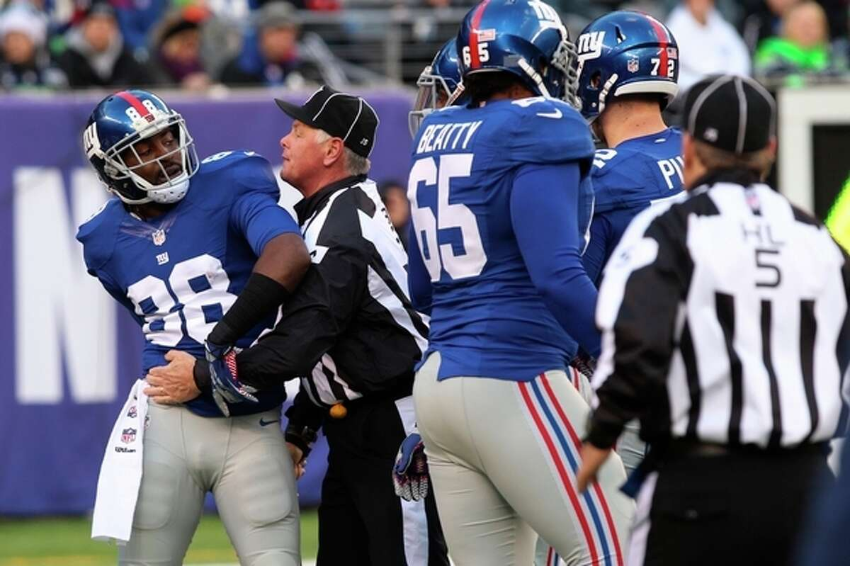 New York Giants wide receiver Hakeem Nicks (88) is restrained by back judge Keith Ferguson during a scuffle between Giants and Seattle Seahawks players on an interception by Seahawks' Richard Sherman at the end of the first half an NFL football game on Sunday, Dec. 15, 2013, in East Rutherford, N.J. (AP Photo/Peter Morgan)