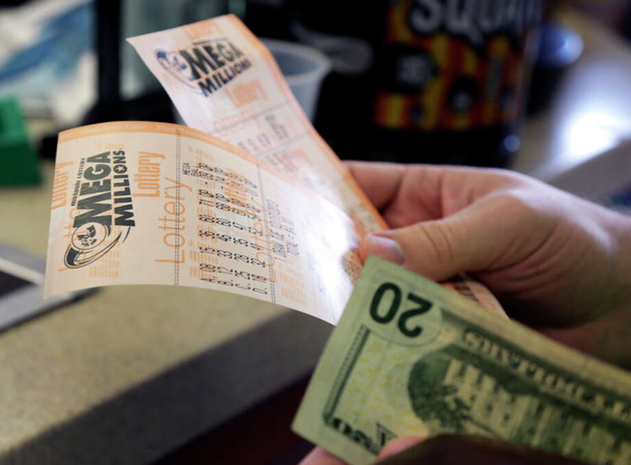 Scott Hoormann holds two Mega Millions lottery tickets he purchased at Energy Express Monday, Dec. 16, 2013, in St. Louis. The Mega Millions jackpot soared to $586 million on Monday amid a frenzy of ticket purchases, a jump that pushed the prize closer to the $656 million U.S. record set last year. (AP Photo/Jeff Roberson) / AP