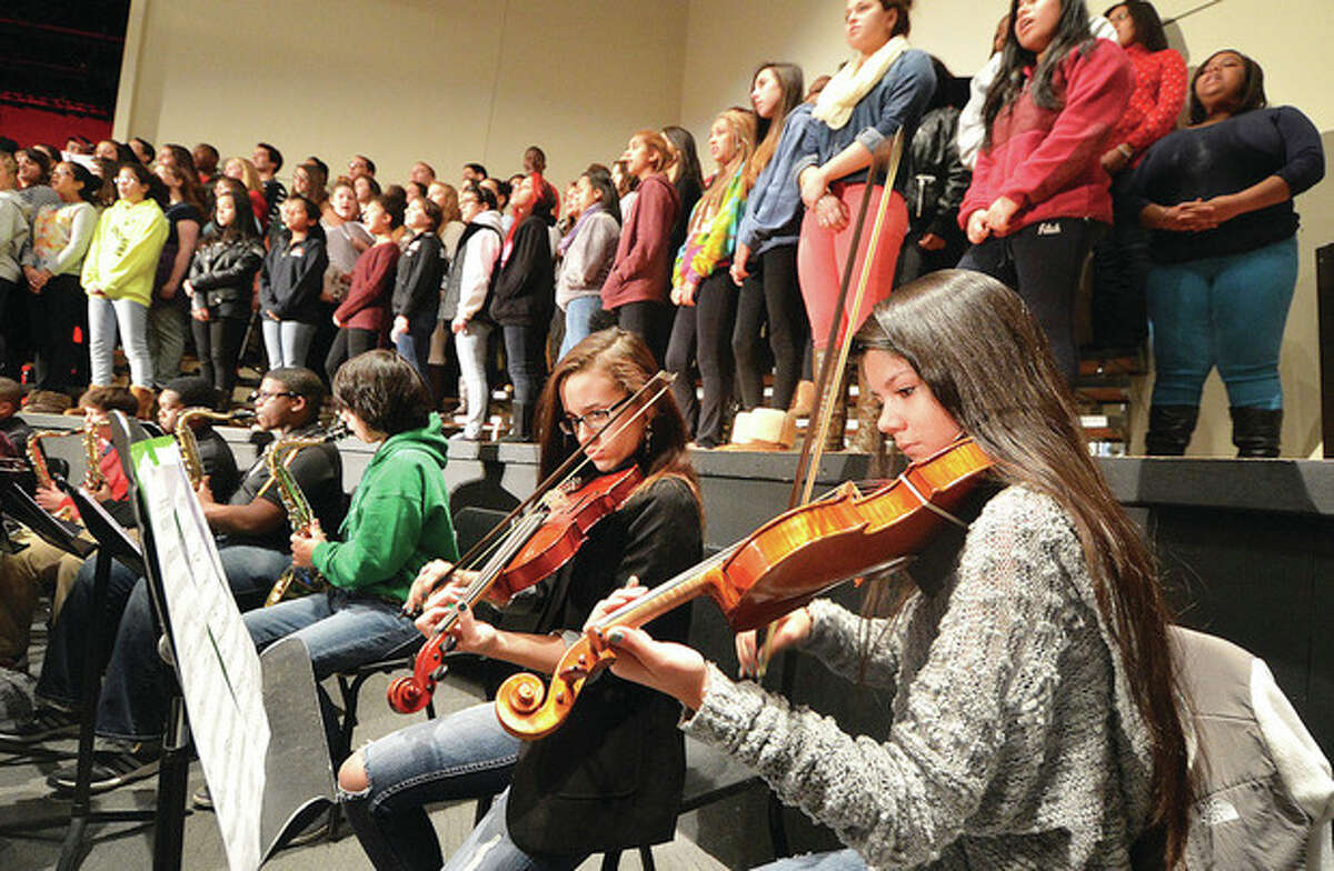 Hour Photo/Alex von Kleydorff. Jennifer Gomez and Hayley Grijalva on strings with the Chorus behind them, during rehearsal for the Poinsettia concert this week at Brien McMahon High School